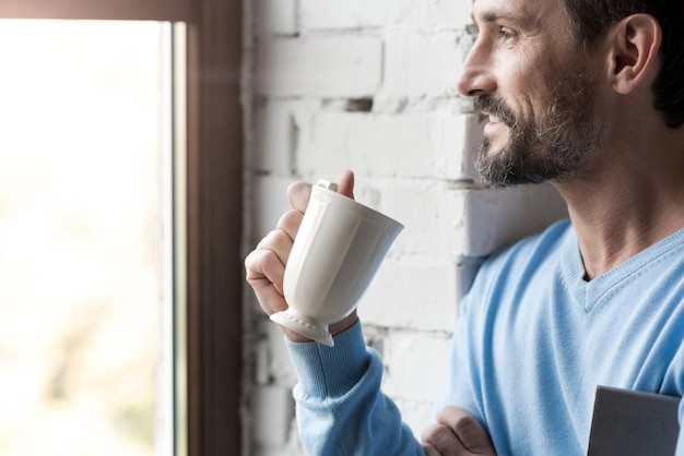 Looking outside. positive handsome cheerful man drinking tea and smiling while looking into the window