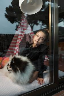 窓の外を見る女の子とふわふわの犬