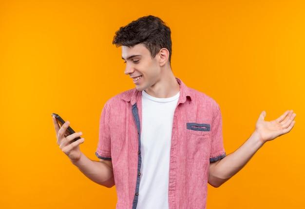 Guardando il telefono sorridente caucasico giovane uomo che indossa la camicia rosa ha alzato la mano sulla parete arancione isolata