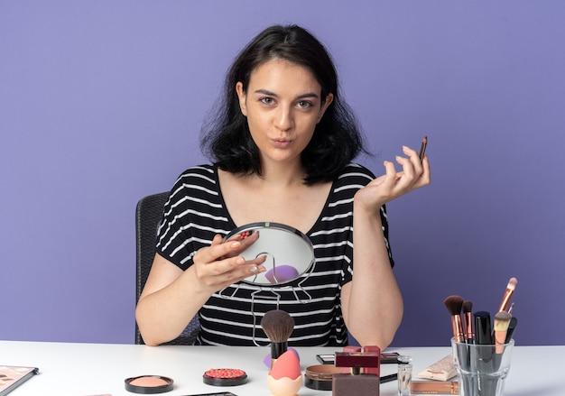 Sembrando contenta la giovane bella ragazza si siede al tavolo con gli strumenti per il trucco che tengono lo specchio con l'eyeliner isolato sulla parete blu