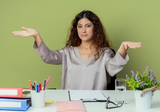 机に座って喜んで若いきれいな女性会社員を見てください。