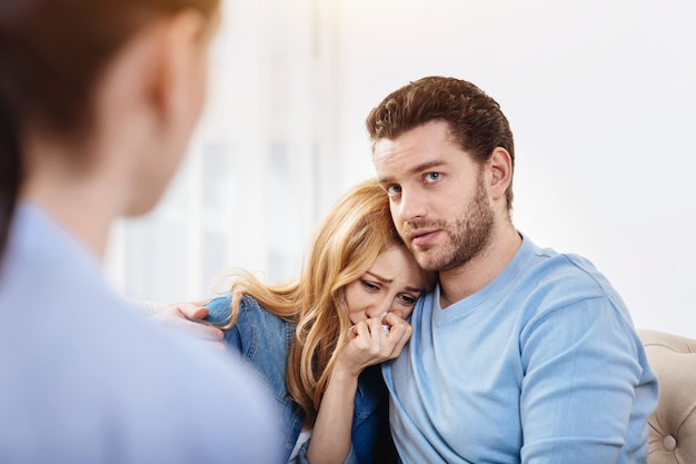 Looking for psychological help. depressed handsome pleasant man hugging his wife and looking at their therapist while looking for psychological help