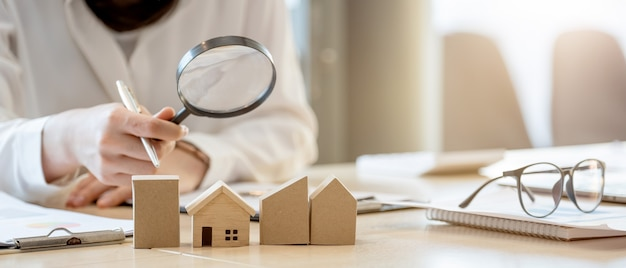 Looking for real estate agency, property insurance, mortgage loan or new house. woman with magnifying glass over a wooden house at her office.