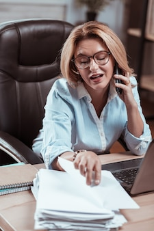 Looking for report. blonde-haired hard-working lawyer wearing glasses speaking by phone and looking for report