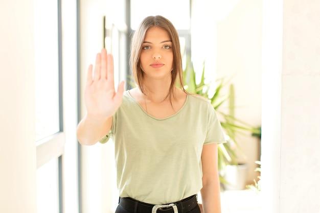 真面目で、厳しく、不機嫌で、怒っているように見え、手のひらを開いて停止ジェスチャーを示しています
