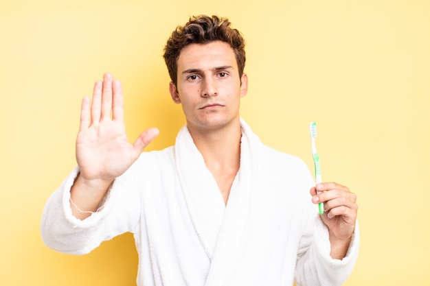 Looking serious, stern, displeased and angry showing open palm making stop gesture. tooth brush concept