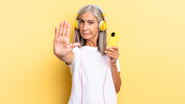 Looking serious, stern, displeased and angry showing open palm making stop gesture with headphones