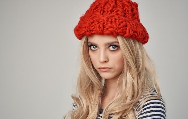Глядя на сексуальных блондинок в красной вязаной шапке и полосатой футболке, обрезанный вид крупным планом.
