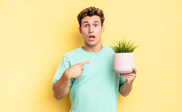 자신을 가리키며 입을 크게 벌리고 놀란 표정을 짓고 있습니다. 장식 식물 개념
