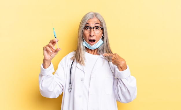 Looking shocked and surprised with mouth wide open, pointing to self. doctor and vaccine concept