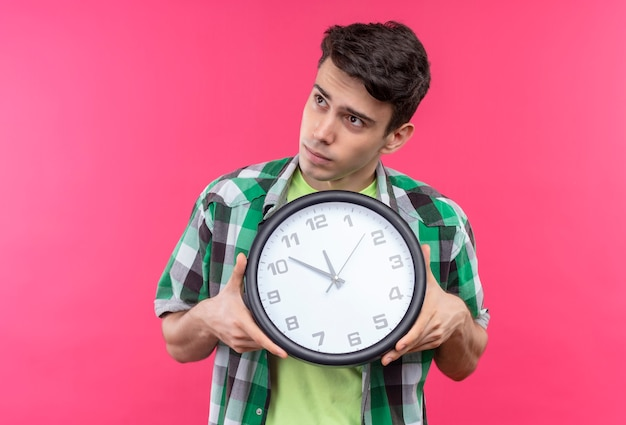 Looking at side caucasian young man wearing green shirt holding wall clock on isolated pink wall
