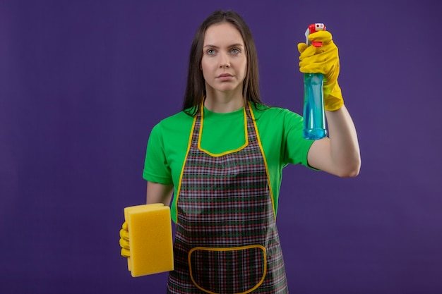 Looking at side cleaning young woman wearing uniform in gloves holding cleaning spray and sponge on purple wall