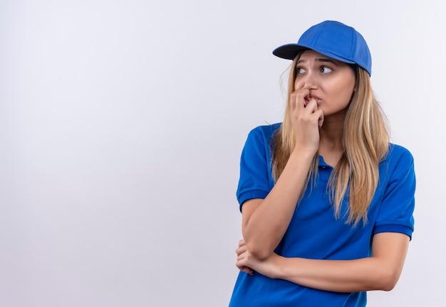 Guardando il lato interessato la giovane ragazza di consegna che indossa l'uniforme blu e il cappuccio che mette la mano sulla bocca isolata sulla parete bianca con lo spazio della copia