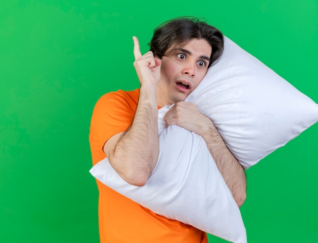 Looking at side concerned young ill man hugged pillow and points at up isolated on green background