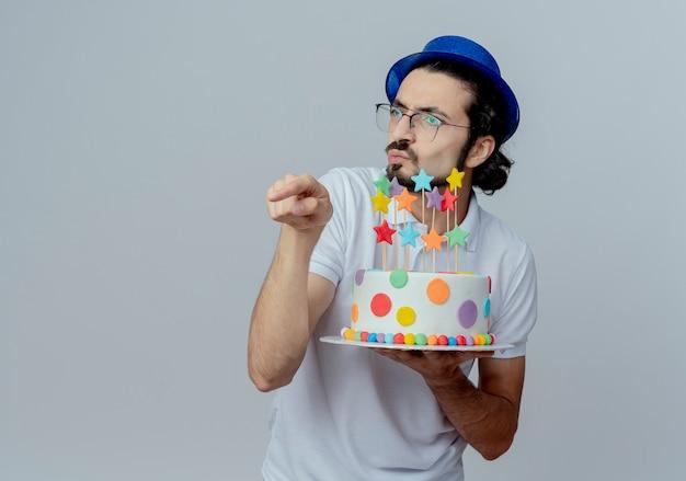 Guardando il lato confuso bell'uomo con gli occhiali e cappello blu tenendo la torta e punti a lato isolato su sfondo bianco con spazio di copia