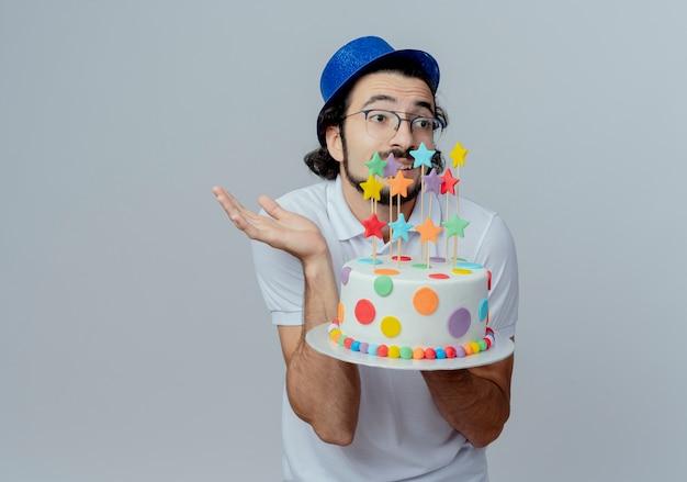 Guardando il lato confuso bell'uomo con gli occhiali e cappello blu tenendo la torta e diffondere la mano isolata su sfondo bianco