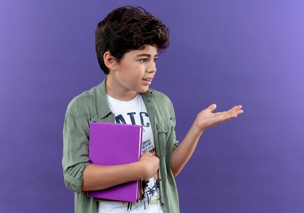 Guardando a lato piccolo scolaro confuso tenendo il libro e punti con la mano a lato