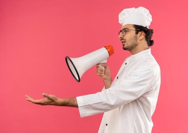 Guardando il lato confuso giovane cuoco maschio che indossa l'uniforme dello chef e gli occhiali parla sull'altoparlante e tendendo la mano a lato