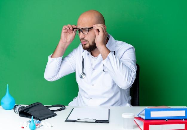 Guardando a lato confuso giovane medico maschio che indossa veste medica e stetoscopio in bicchieri seduto alla scrivania con strumenti medici isolati su sfondo verde