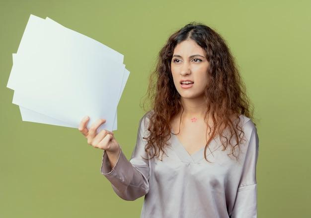 Guardando il lato confuso giovane impiegato abbastanza femminile che tiene i documenti isolati sulla parete verde oliva