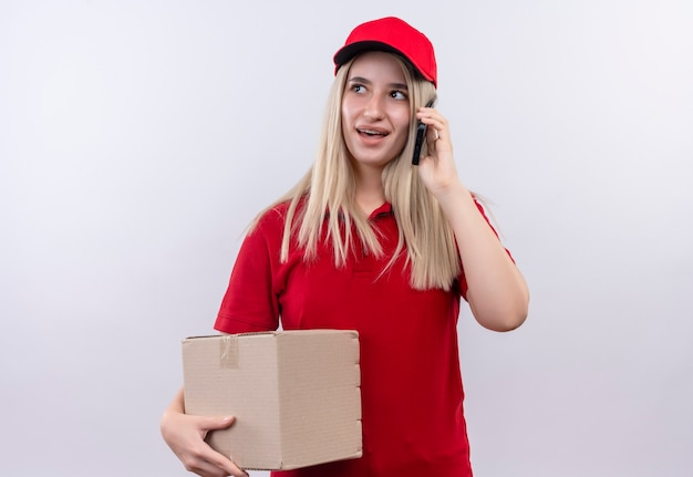 Looking at side delivery young woman wearing red t-shirt and cap in dental brace holding box and pseakes on phone on isolated white wall