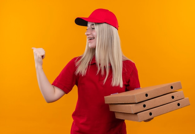 Looking at side delivery young woman wearing red t-shirt and cap holding pizza box showing yes gesture on isolated orange wall