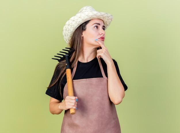 Guardando il lato impressionato bella ragazza giardiniere in uniforme che indossa cappello da giardinaggio tenendo il rastrello