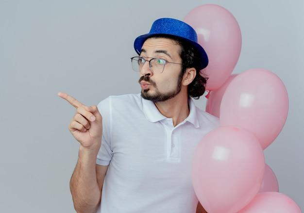 Guardando il lato impressionato bell'uomo con gli occhiali e cappello blu che tiene palloncini e punti a lato isolato su sfondo bianco con spazio di copia