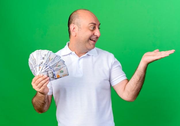 Guardando il lato gioioso casual uomo maturo che tiene contanti e punti con la mano a lato
