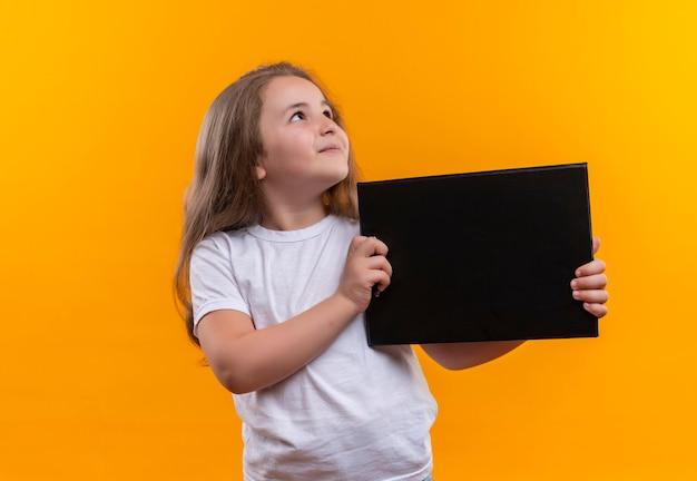 Esaminando la piccola scuola laterale che indossa la lavagna per appunti bianca della tenuta della maglietta sulla parete arancio isolata