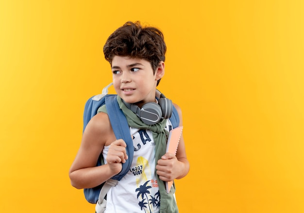 Looking at side pleased little school boy wearing back bag and headphones holding notebook  isolated on yellow background with copy space