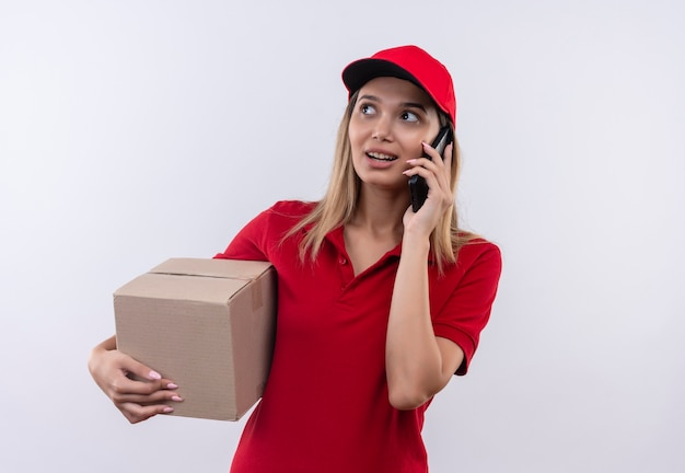 Looking at side pleased young delivery girl wearing red uniform and cap holding box and speaks on phone  isolated on white wall