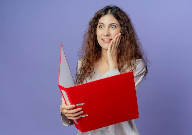 Guardando il lato soddisfatto giovane ragazza graziosa che tiene la cartella e mettendo la mano sulla guancia isolata sulla parete blu