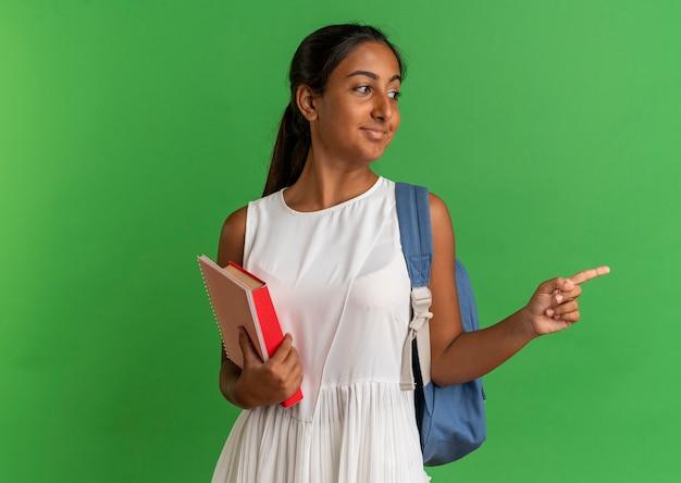 Guardando il libro da portare della tenuta dello zaino della giovane scolara soddisfatta di lato con il taccuino ed i punti a lato