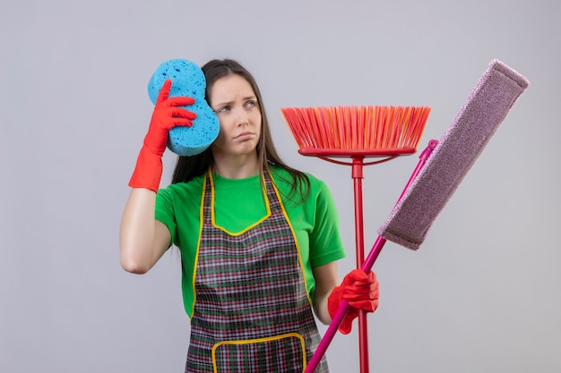 Looking at side sad cleaning young woman wearing uniform in red gloves holding cleaning tools on isolated white wall