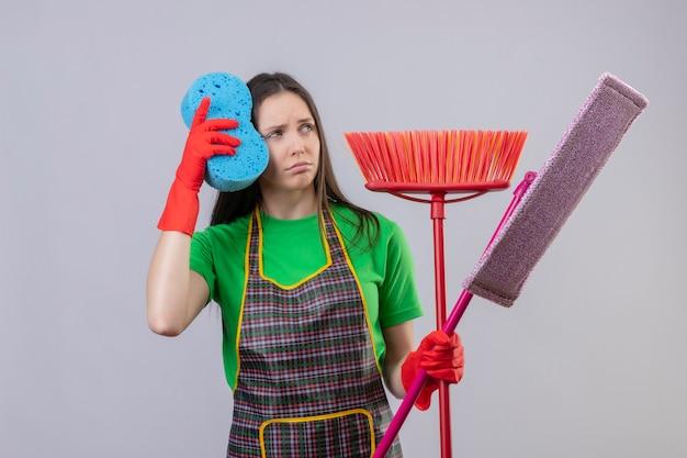 Guardando il lato triste pulizia giovane donna che indossa l'uniforme in guanti rossi che tengono gli strumenti di pulizia sulla parete bianca isolata