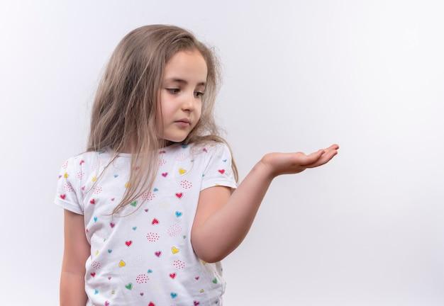 Guardando la piccola ragazza triste della scuola laterale che porta la maglietta bianca che solleva la mano sulla parete bianca isolata