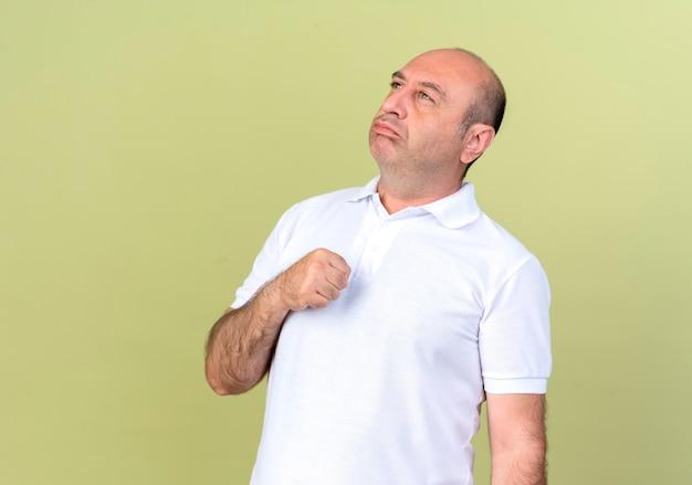 Guardando il lato triste uomo maturo tenendo il pugno intorno al petto isolato su sfondo verde oliva