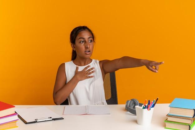 Guardando di lato la giovane studentessa spaventata seduta alla scrivania