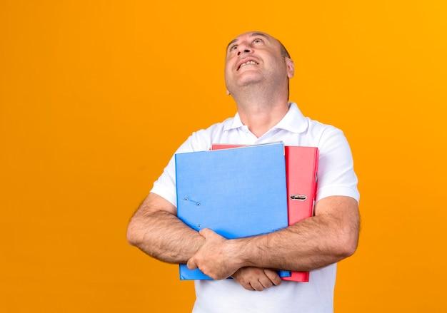 Guardando il lato sorridente casual uomo maturo che tiene le cartelle isolate sulla parete gialla con lo spazio della copia