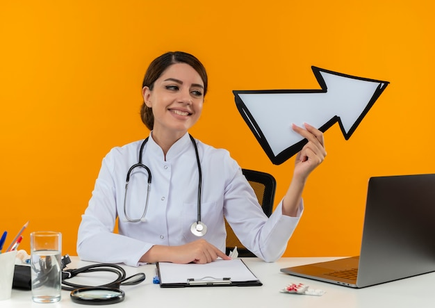 Looking at side smiling young female doctor wearing medical robe with stethoscope sitting at desk work on computer with medical tools holding direction mark on isolation yellow wall