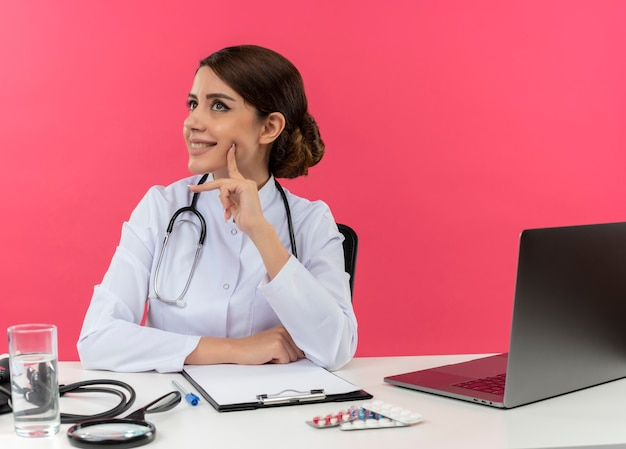Looking at side smiling young female doctor wearing medical robe with stethoscope sitting at desk work on computer with medical tools putting finger on cheek on pink wall with copy space