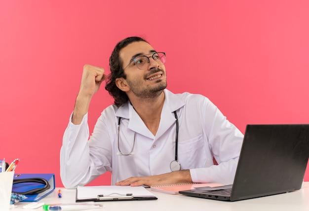 Guardando al lato sorridente giovane medico maschio con occhiali medici che indossano accappatoio medico con stetoscopio seduto alla scrivania
