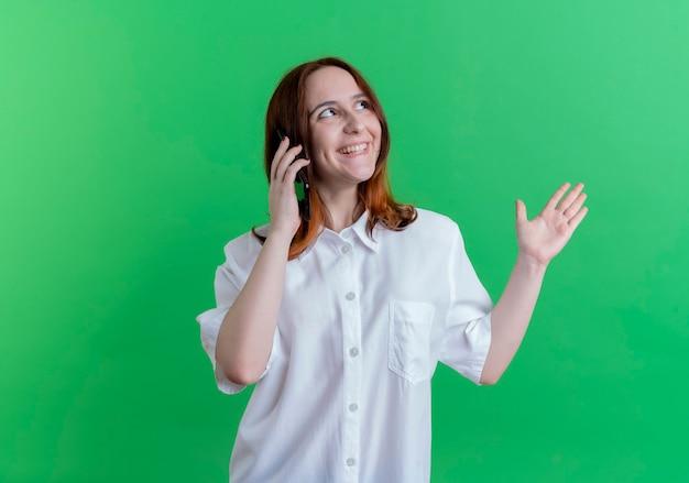 Guardando il lato sorridente giovane ragazza rossa parla sui punti di telefono con la mano a lato isolato su sfondo verde con spazio di copia