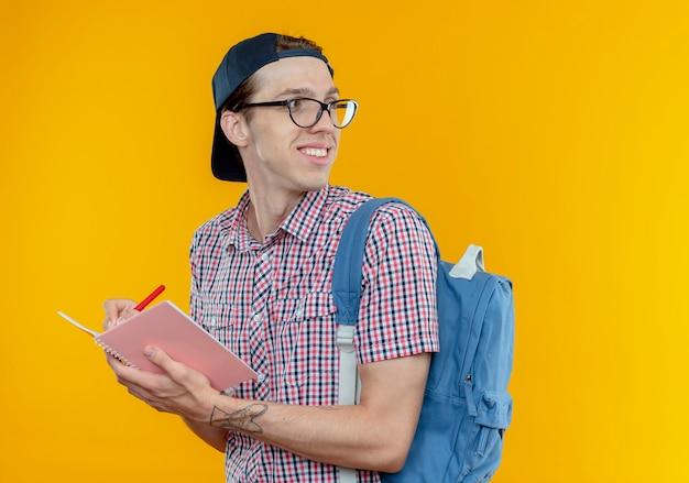 Guardando il lato sorridente giovane studente ragazzo indossa borsa posteriore e occhiali e berretto in possesso di taccuino e penna isolato su sfondo bianco