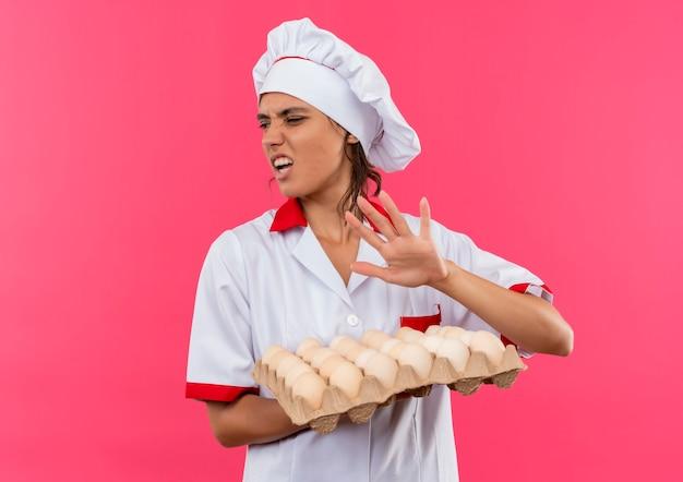 Guardando il lato schizzinoso giovane cuoco femminile che indossa l'uniforme dello chef tenendo il lotto di uova sulla parete rosa isolata con lo spazio della copia