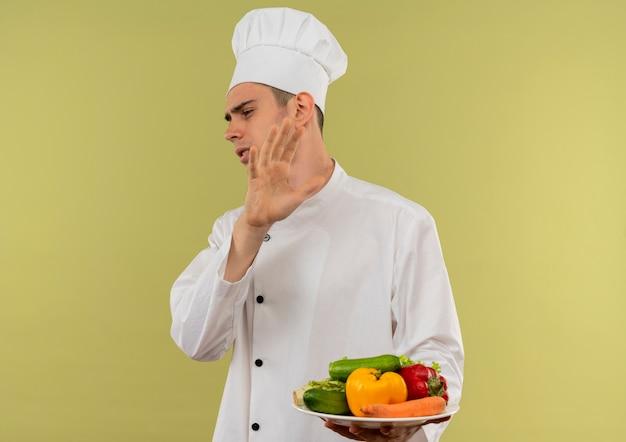 Guardando il lato schizzinoso giovane cuoco maschio che indossa l'uniforme dello chef tenendo le verdure sul piatto che mostra il gesto di arresto sulla parete verde isolata