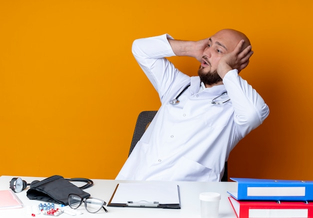 Looking at side surprised young bald male doctor wearing medical robe and stethoscope sitting at work desk with medical tools grabbed head isolated on orange background