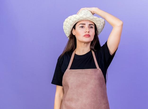 Guardando a lato pensando bella ragazza giardiniere in uniforme che indossa il cappello da giardinaggio mettendo la mano sul cappello isolato su sfondo blu con copia spazio