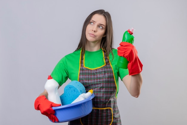 Looking at side thinking cleaning young woman wearing uniform in red gloves holding cleaning tools on isolated white wall